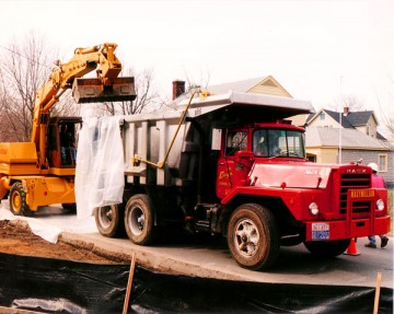 Workers load the back of a dump truck with contaminated soil.